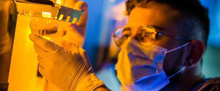 Un técnico de Dental Astur examina una prótesis elaborada en la impresora 3D.